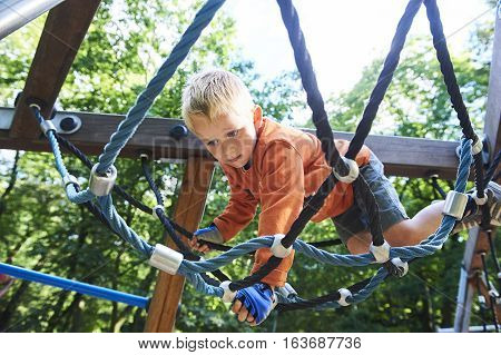 Little child boy climbing rope on the playground outdoors
