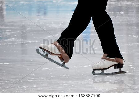 Feet and skates of ice skater at outdoor skating rink in New York City