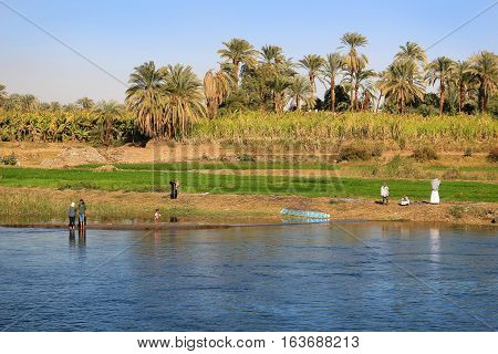 Nile River Egypt - February 3 2016: People along the shore of the Nile River in Egypt Africa