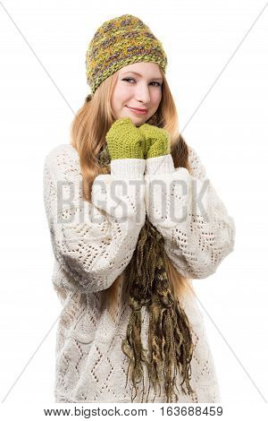 Young stylish smiling blonde woman in variegated melange knitted hat scarf with fringe mittens and long patterned white sweater props up her chin by hands isolated on white background.