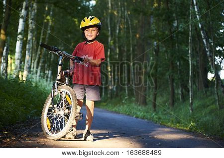 A young child boy walking at bicycle in bike path in summer day
