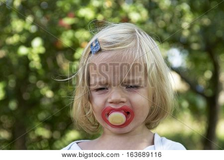 Portrait of little child baby crying girl, natural background. Baby with a pacifier in his mouth