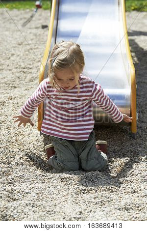 Cute little girl sliding on public playground