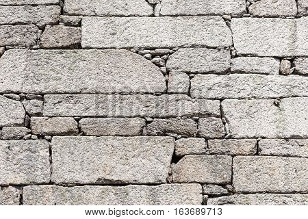 Massive blocks of stone wall, natural background material, detail outdoor stone wall jointless