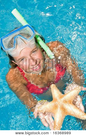 Snorkel girl with starfish on summer vacation