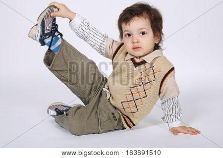 photo of little boy doing exercises on white