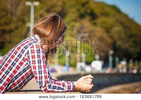 Man long hair alone on sea shore lost in thought is concerned and stressed about events in his life. Unemployment depression concept