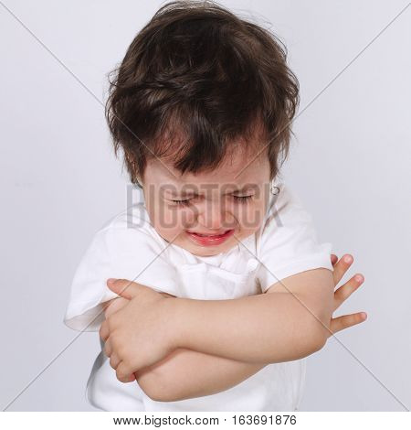 photo of cute crying boy on white background