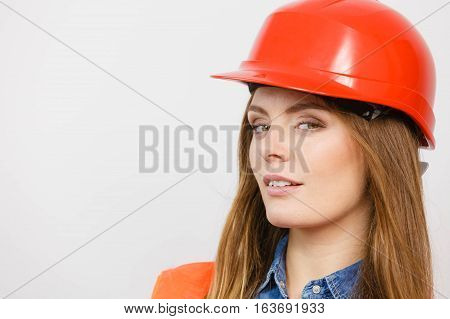 Woman construction worker builder structural engineerin in red hard helmet. Safety in industrial work. Studio shot
