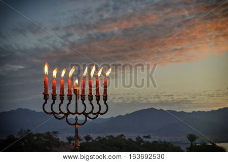 Menorah with glitter lights of candles is traditional symbol for Jewish Hanukkah Holiday Photo was taken at sunrise using the nine burning decorative candles as foreground for inspiration of Jewish symbols for Hanukkah holiday. Selective focus