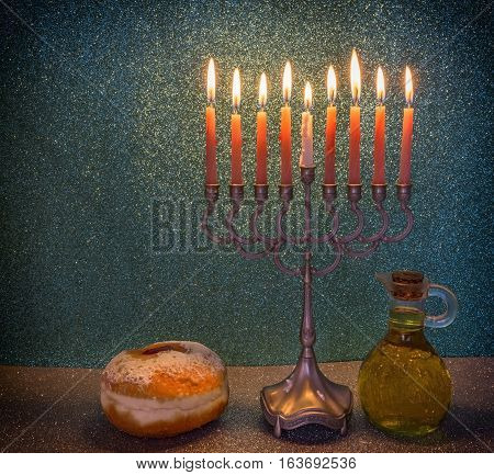 Menorah with glitter lights of candles and sweet donuts are traditional symbols for Jewish Hanukkah Holiday