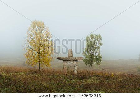Two trees on a fall morning in the fog with a stone inukshuk