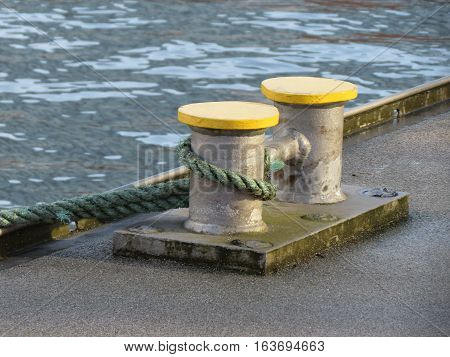 Double mooring bollard with a rope by a canal