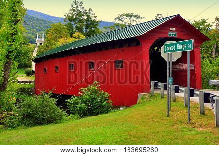 West Arlington Vermont - September 17 2014: 1852 Red Covered Bridge over the Battenkill River and United Methodist village church