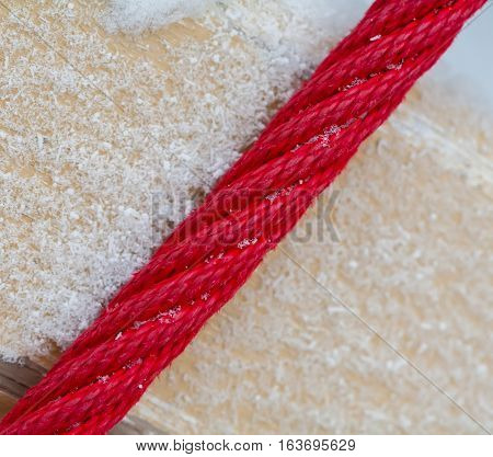 Red rope on the background of yellow boards. Board covered with snow. The diagonal arrangement.