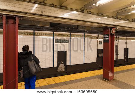 NEW YORK - APRIL 27 2016: Unkknown traveler waiting for the subway to come on Fulton street subway platform