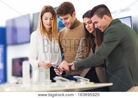 Four people are choosing smart phones in store