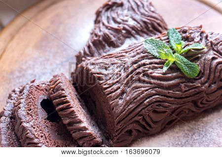 Yule log with icing on the wooden board