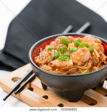 Closeup view of spicy chicken pad thai on a bamboo trivet.