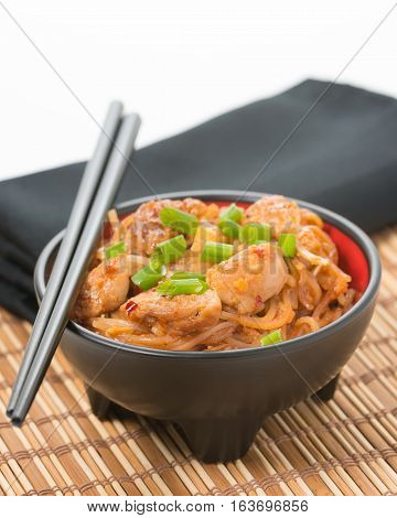 Spicy chicken pad thai in a black bowl on a bamboo placemat.