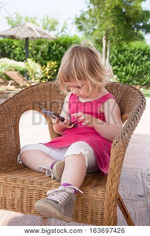 blonde caucasian girl two years old in summer red dress sitting on wicker chair watching and touching with finger smartphone or mobile phone