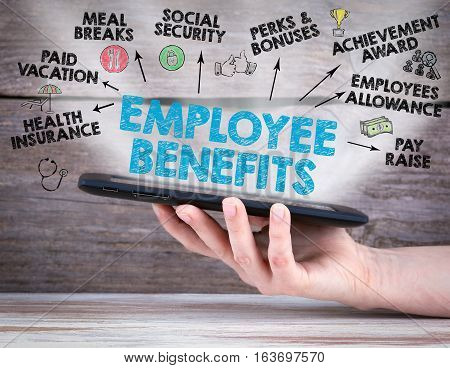 Employee Benefits Concept. Tablet computer in the hand. Old wooden background.