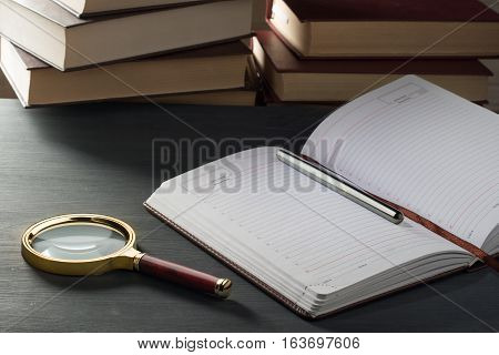 Notepad In The Box With A Pen On A Wooden Table In The Background Of A Stack Of Books.