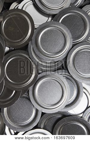 Industrial background. Close up of metal car parts in a warehouse. Stack of new and shiny steel lids in factory.
