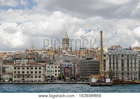 ISTANBUL TURKEY - JUNE 8 2016: Crowds enjoying the sea breeze from the Bosphorus at the Karakoy area in Istanbul. The Byzantine Galata Tower dominates the top of the scene.