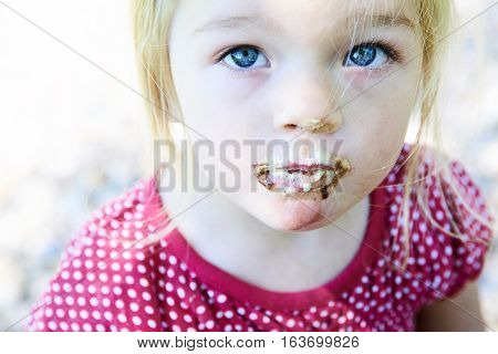 Beautiful little child blond girl with blue eyes eats ice cream in the summer.