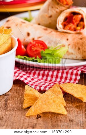 Tortilla wraps with chicken and vegetable on white dish.