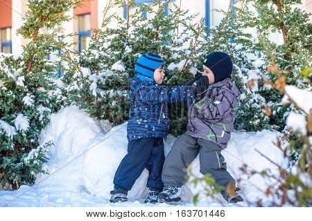 Two Little Kid Boys In Colorful Clothes Playing Outdoors During Snowfall. Active Leisure With Childr