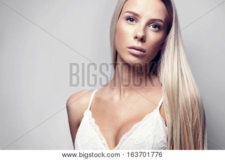 Fashion studio photo of a beautiful young woman with blonde hair in a white see-through bodysuit. Wearing in nightware.