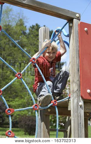 Little child blond boy climbing rope web on the playground outdoors