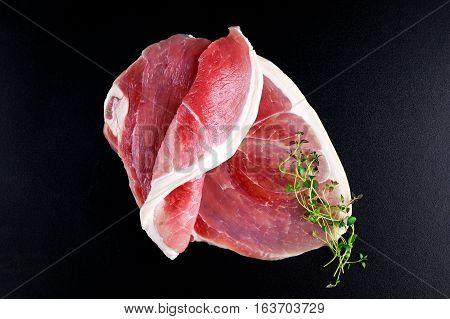 Raw gammon steak on black background with thyme.