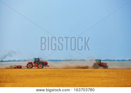 Summer day two tractors to plow plow the soil on sloping cornfield. Agricultural land treatment before planting.