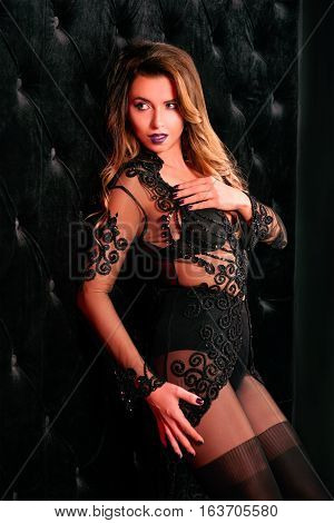 Young beautiful attractive and hot long hair woman in black underwear near black velvet wall in photo studio