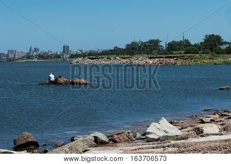 fisherman on the rocks in the river, uruguayan coast