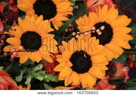 Big yellow sunflowers and orange roses in a floral wedding decoration