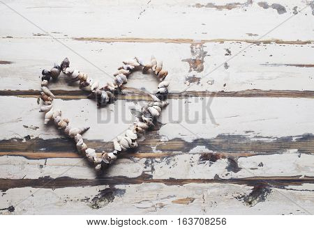 heart made of shells on a white wooden background, selective focus