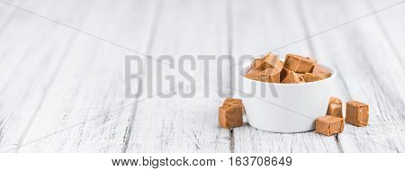 Portion Of Caramel Pieces On Wooden Background (selective Focus)