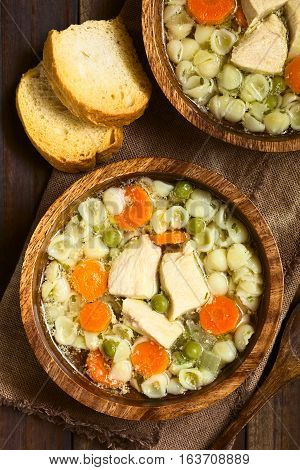Homemade chicken soup with pea carrot and small shell pasta in wooden bowls with toasted bread on the side photographed overhead on dark wood with natural light (Selective Focus Focus on the top of the soups)