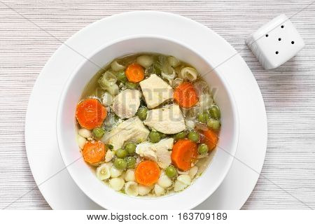 Homemade chicken soup with pea carrot and small shell pasta in bowl photographed overhead with natural light (Selective Focus Focus on the top of the soup)