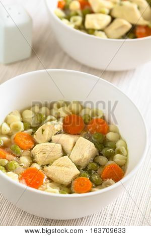 Homemade chicken soup with pea carrot and small shell pasta in bowls photographed with natural light (Selective Focus Focus in the middle of the first soup)
