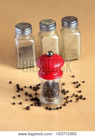 Still life with black peppercorn, hand mills and glass spice jars on wooden surface. Photo closeup