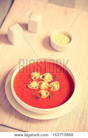 Homemade fresh cream of tomato soup with tortellini garnished with fresh oregano leaves photographed with natural light (Selective Focus Focus in the middle of the soup) (Digitally Altered: Toned Image)