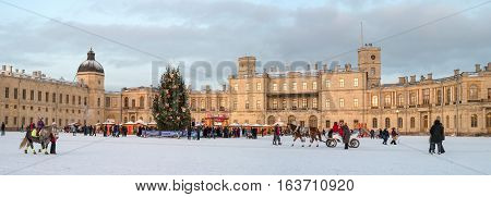 Gatchina, Russia - January 2, 2017: Gatchina Palace, New Year's Fair on the parade ground. Panorama on the background of the palace with a Christmas tree, fair. Photo taken in the evening.