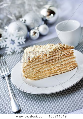 Piece of layer cake with custard and walnuts on a plate with Christmas balls on the background