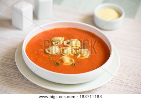 Homemade fresh cream of tomato soup with tortellini garnished with fresh oregano leaves photographed with natural light (Selective Focus Focus in the middle of the soup)