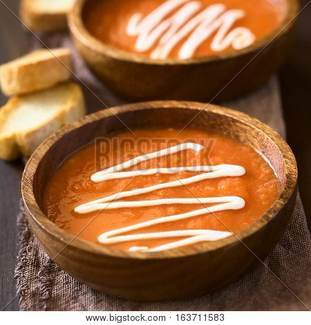 Homemade fresh cream of tomato soup served in wooden bowls with toasted bread slices on the side photographed with natural light (Selective Focus Focus in the middle of the first soup)